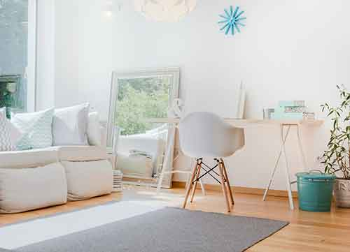 Image of nicely decorated white room with desk and rug
