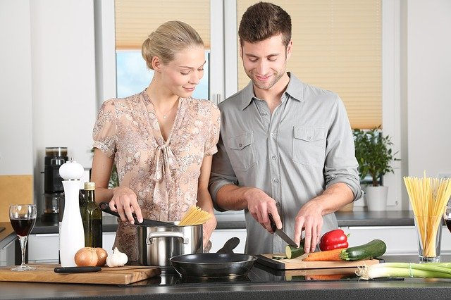 men and woman cooking at home