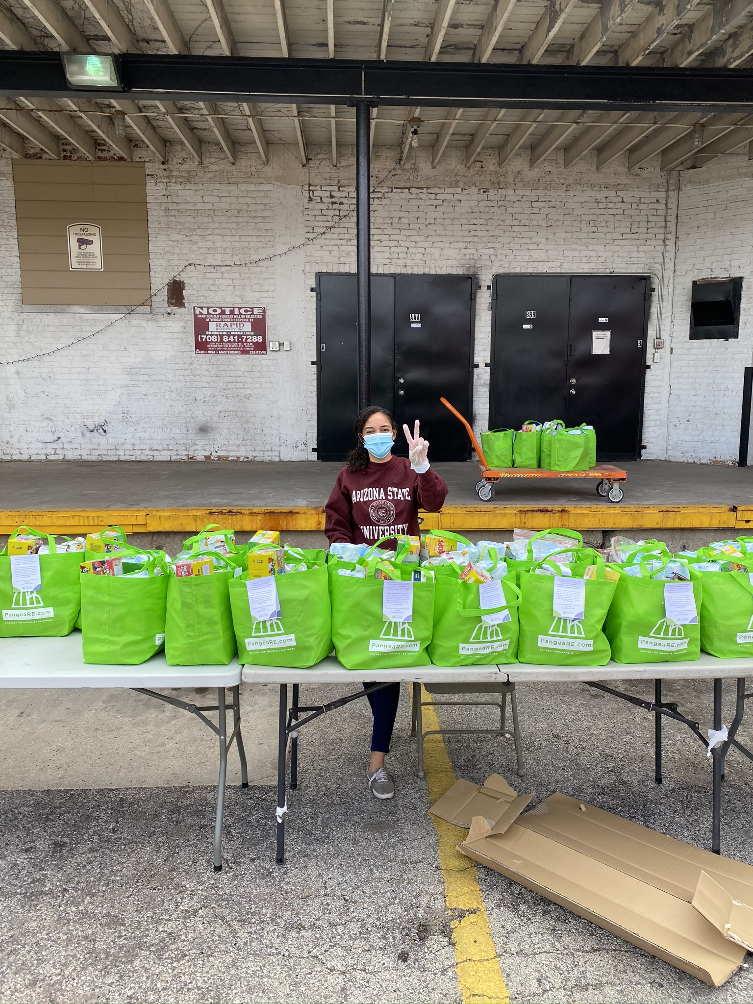 Pangea Cares Program Director, Chanelle Cromwell standing behind care packages waiting to be delivered