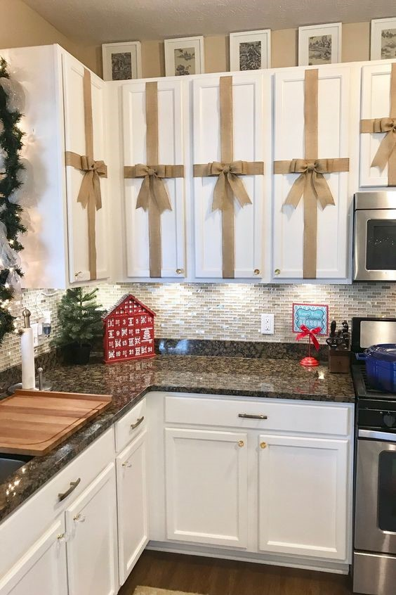 kitchen decorated for the holidays with ribbons on the cabinets