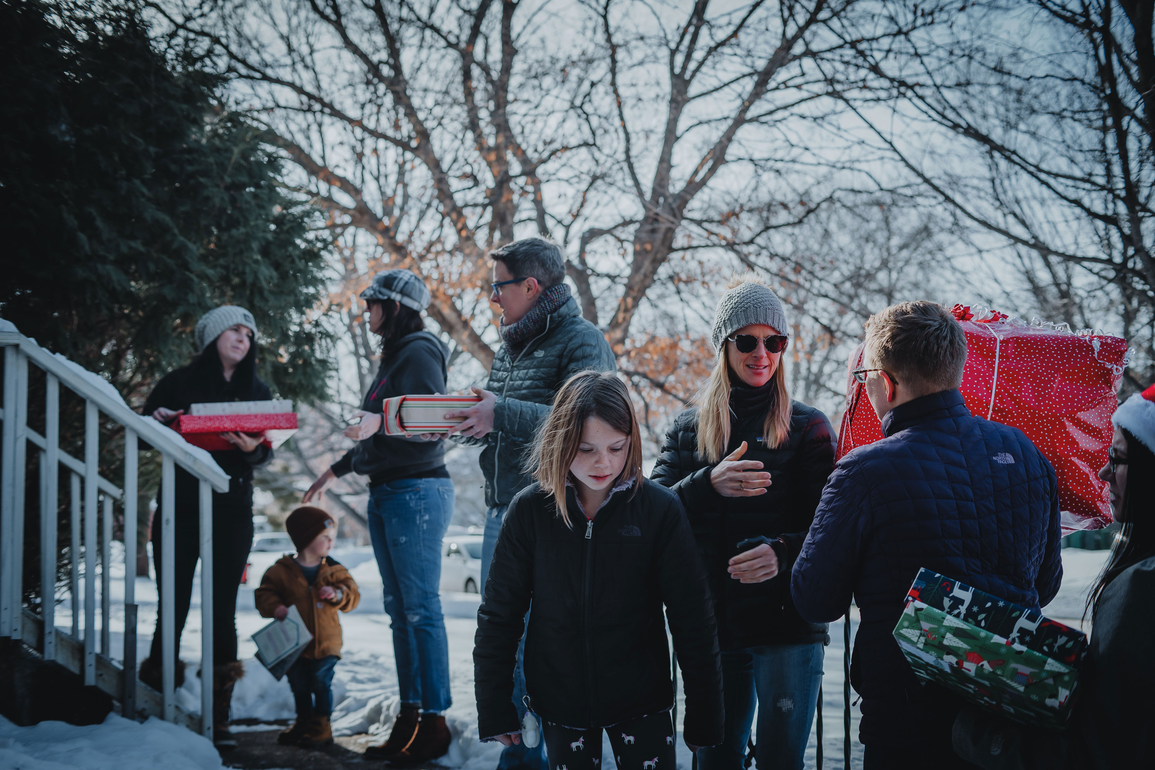 Adults and children line up outside a family home in Minnesota to deliver gifts in December 2019 as part of CIP's sponsorship of Best Christmas Ever 2019
