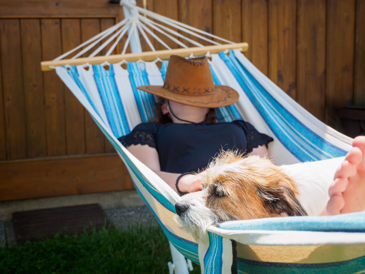 Young woman with dog in a hammock in the garden