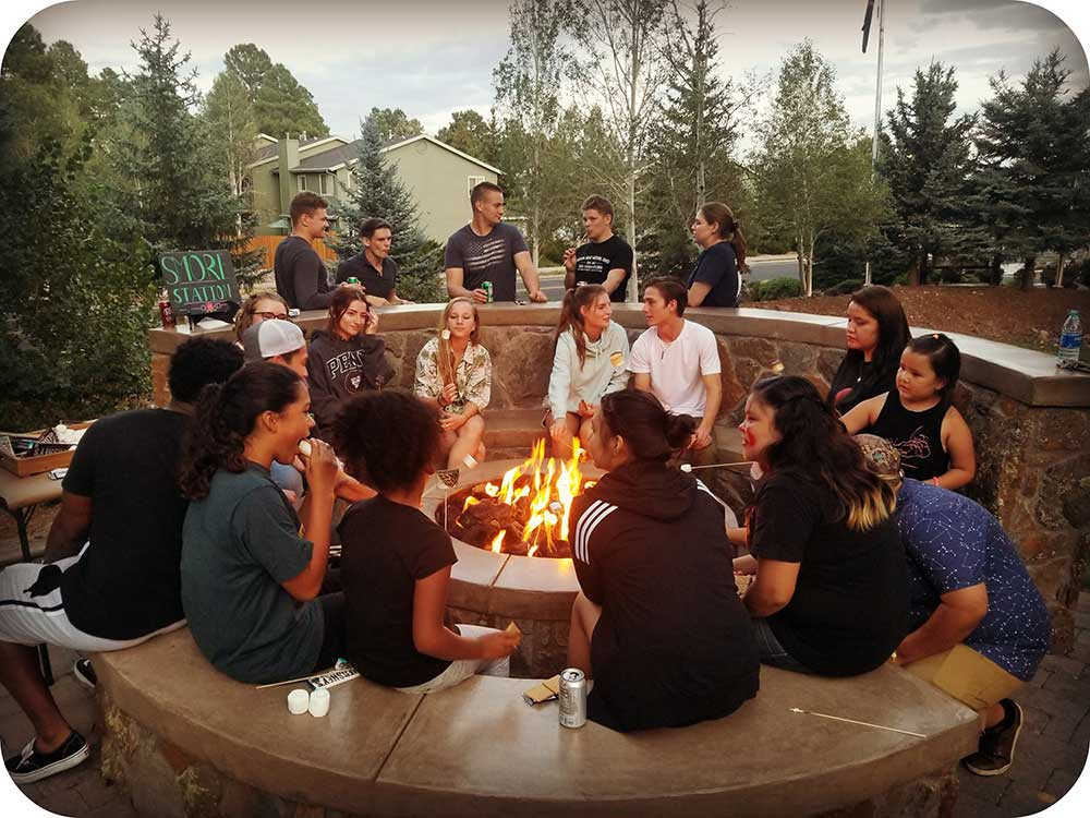 Residents gathering around the fire pit for a community event.