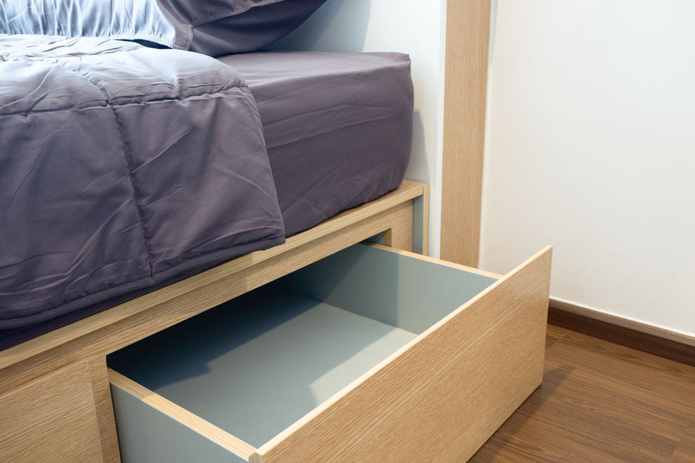 Using a bed frame with space or drawers underneath is a great storage hack for your Weidner Apartment Home.