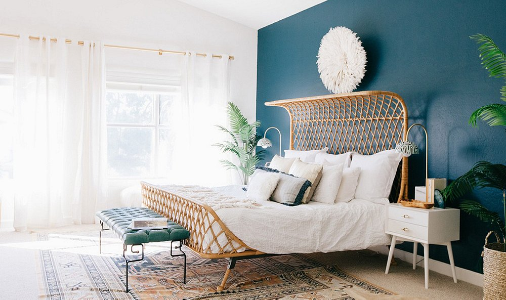 unique bedframe in an open bedroom with a blue accent wall