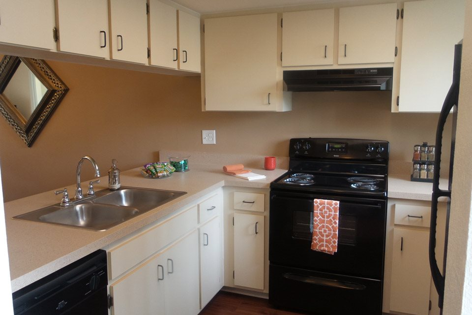 Kitchen with black appliances and white cabinets | Bay Club Apartments