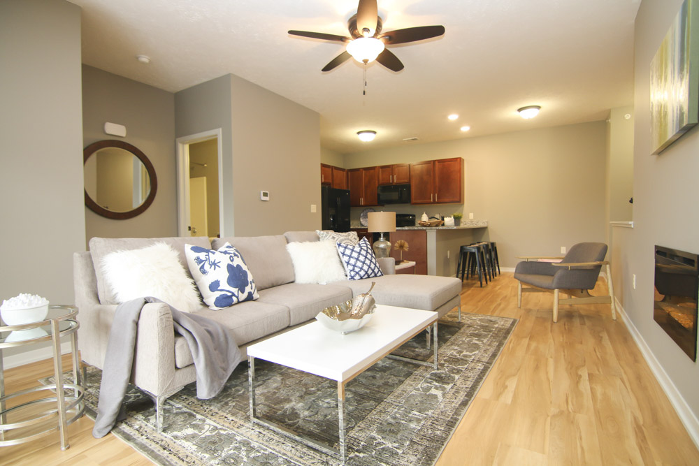 Furnished living room with sofa, coffee table and cozy fireplace at The Villas at Wilderness Ridge.