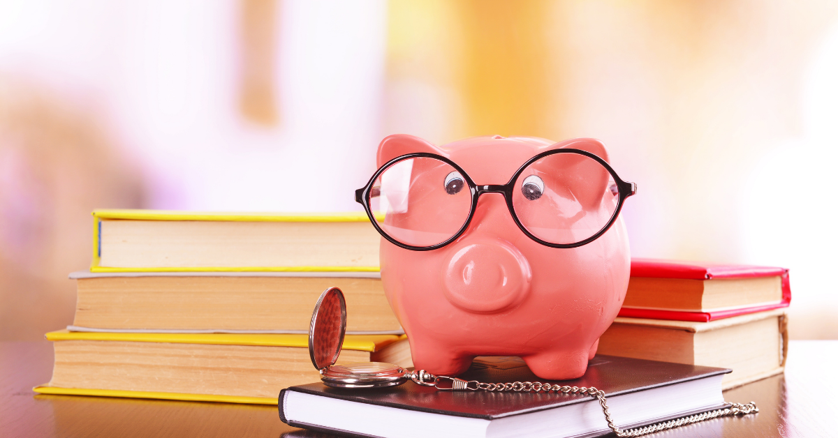 a photograph of a piggy bank wearing glasses standing on a stack of books to imply financial literacy month