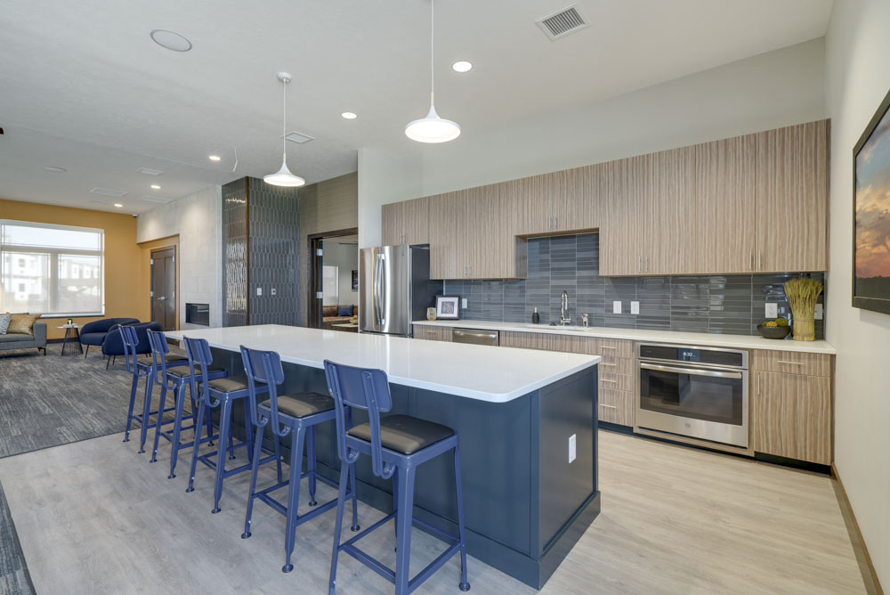 Modern kitchen with island seating in the furnished clobhouse at WH Flats apartments in southwest Lincoln NE 68516