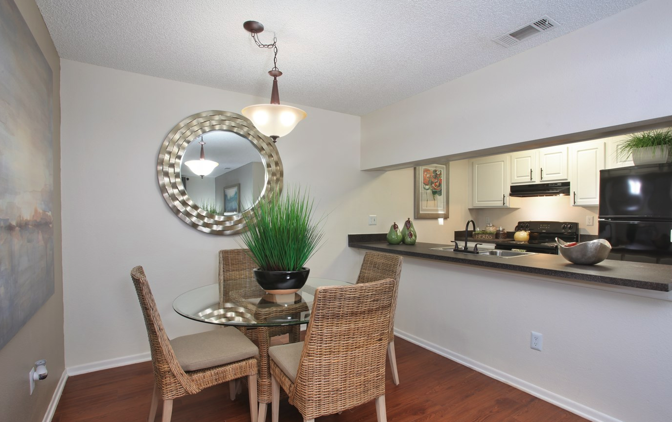 Dining Area with Open View into Kitchen with modern black appliances | Coral Club Apartments