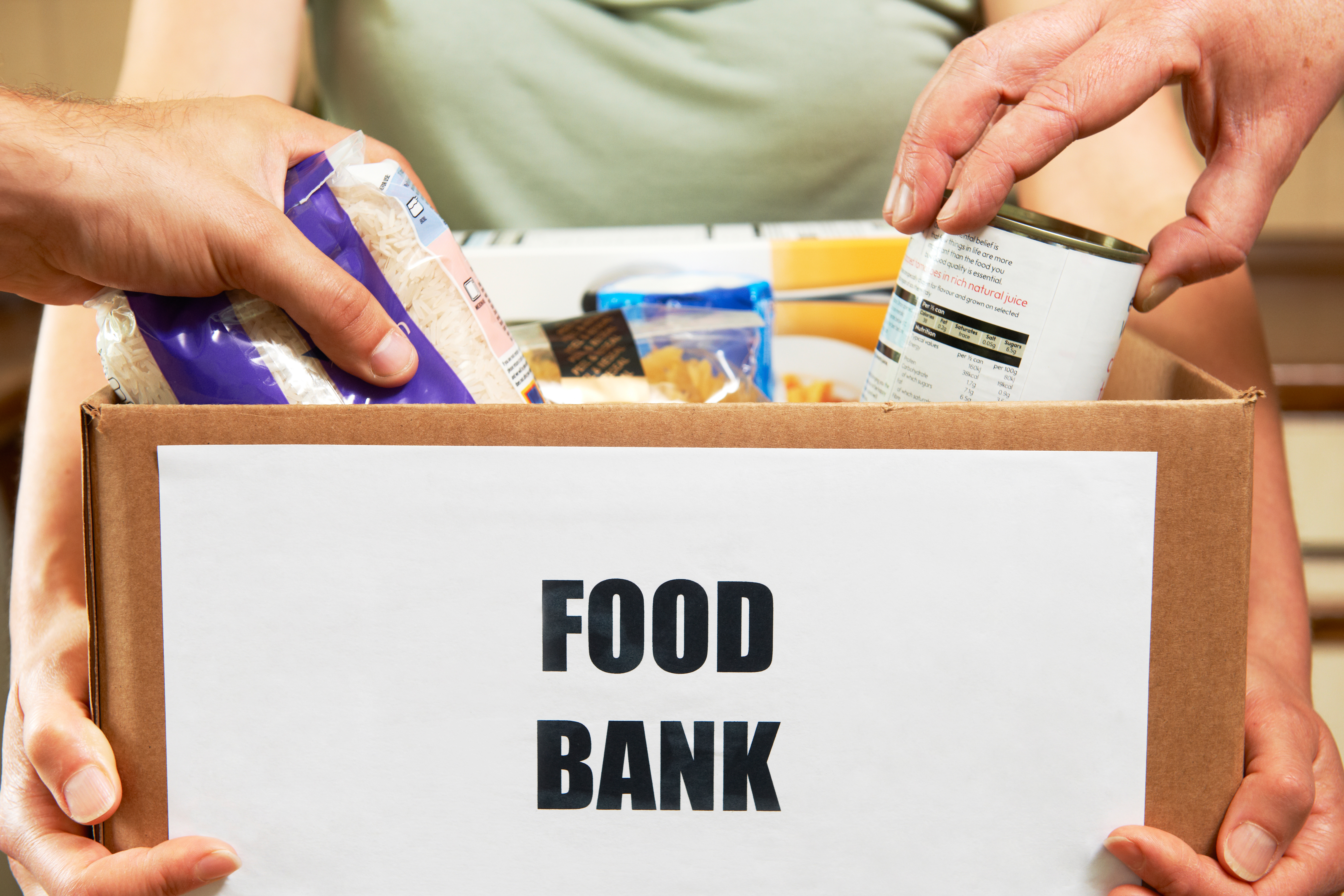 "Lady holding box with ""food bank"" sign on the front"