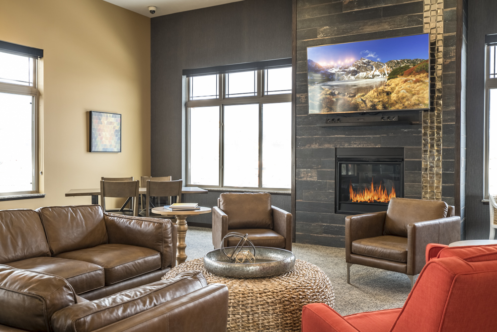 Apartment clubhouse with cozy seating, a fireplace and mounted TV at 360 at Jordan West in West Des Moines, IA