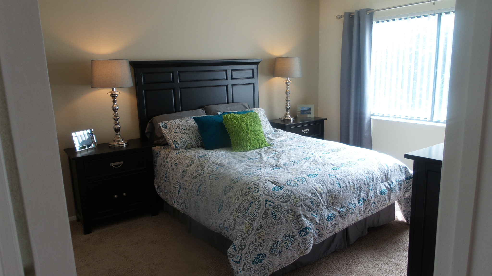 Bedroom with large bed, nightstands and natural light from window | Bay Club Apartments