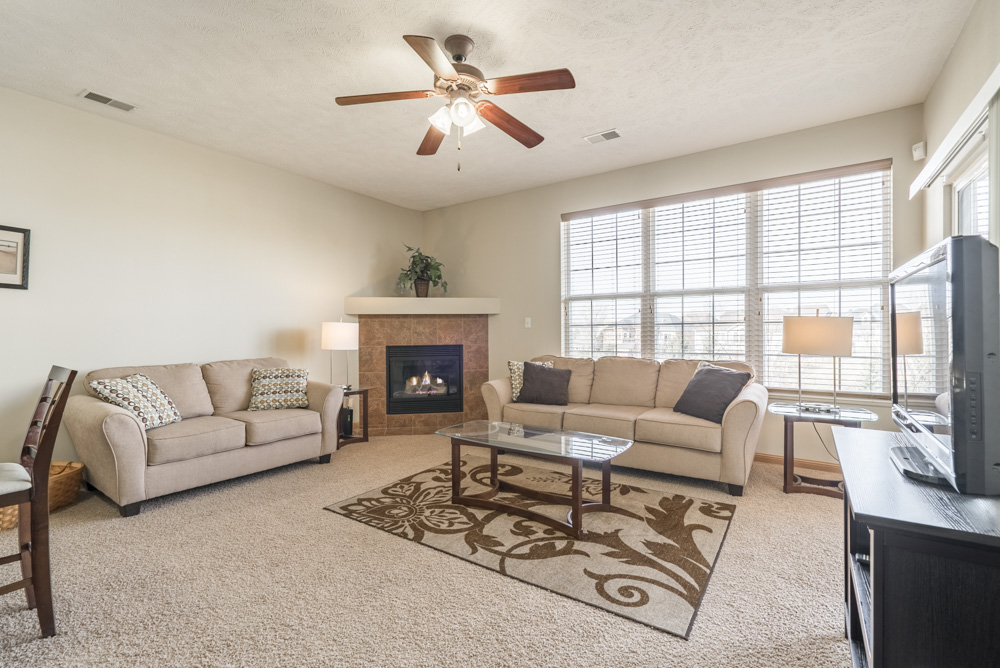 Furnished living room with cozy corner fireplace at Stone Ridge Estates in Lincoln NE