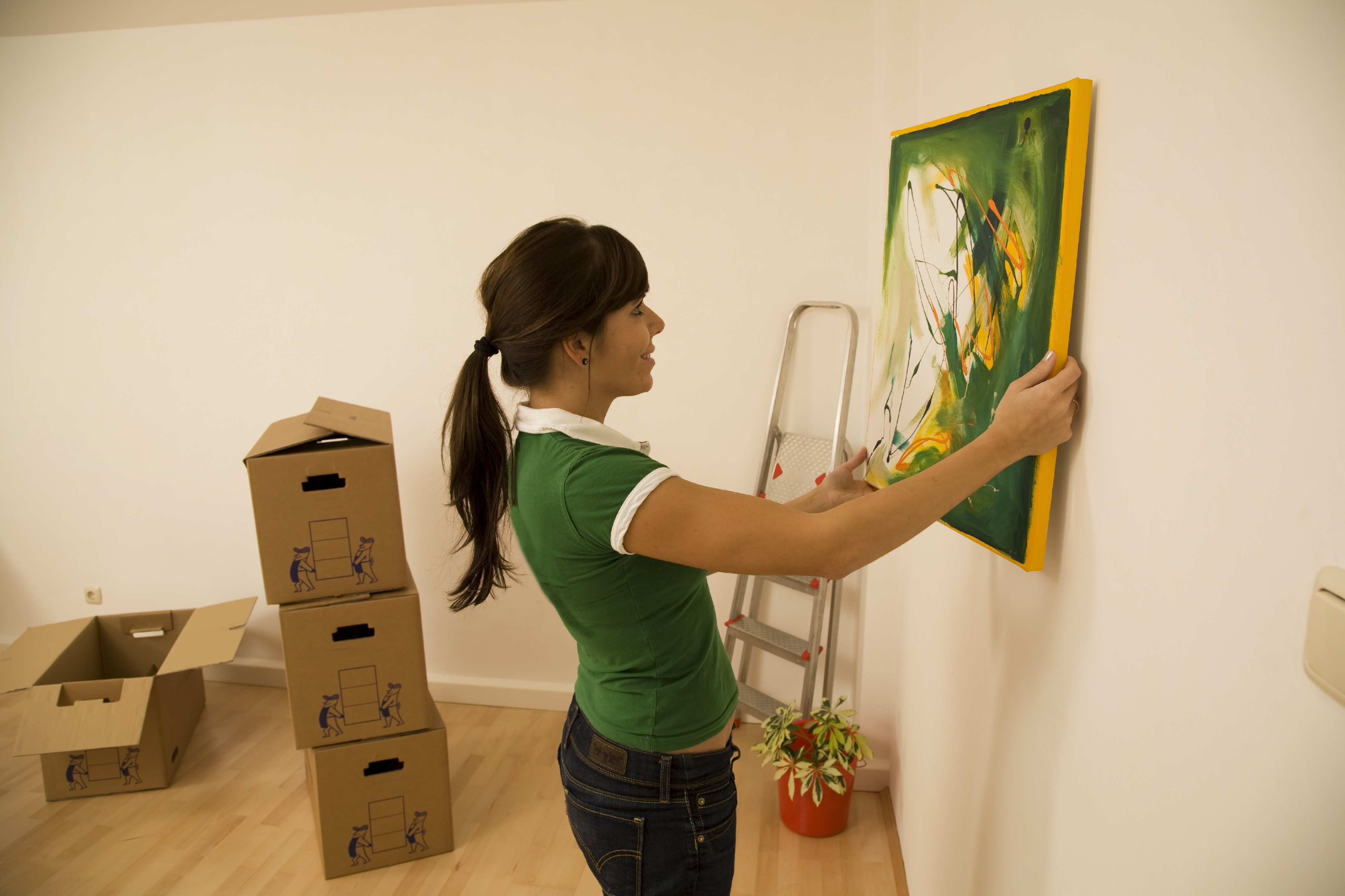 woman hanging art in her apartment