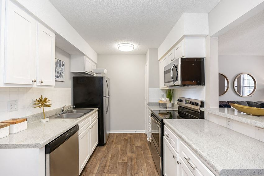 Renovated Galley Kitchen with White Cabinets and Stainless Steel Appliances