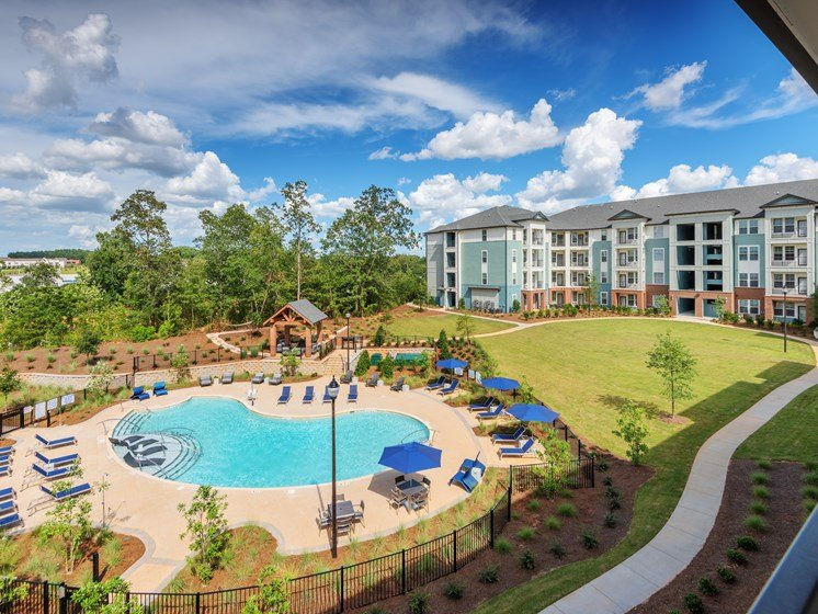Greenville Apartments for Rent-Trailside Verdae Apartments Overhead View Of Large Gated Pool Surrounded By Lush Landscaping