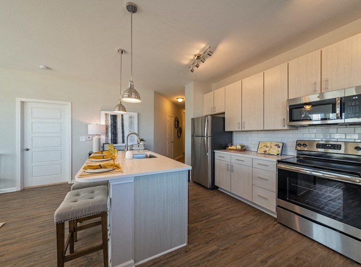 Dayton Apartments-Tapestry On The River Apartments Kitchen With Spacious Island With Seating And Wood-Style Flooring