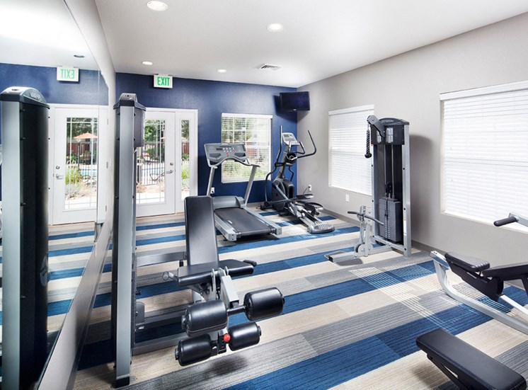 Ardenne Apartments fitness center with weight machines, treadmill, elyptical, blue and white carpet and blue accent wall