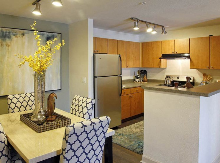 Ardenne Apartments kitchen and dining room with blue and white chairs, yellow flowers and stainless steel appliances