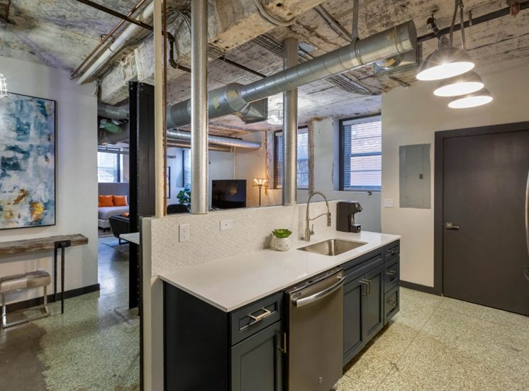 Industrial Style Apartment with Exposed Concrete and Ducts, Kitchen with White Counters, Blue Cabinets, Bar Style Table with Stools Under Art with Open Layout in the Background
