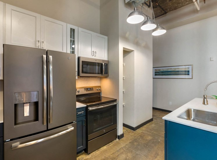 Industrial Style Apartment with Exposed Concrete and Ducts, Kitchen with Breakfast Bar, White Upper Cabinets and Dark Blue Lower Cabinets Around Stainless Steel Appliances Next to Built in Shelves