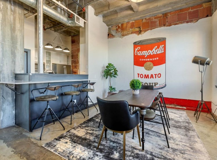 Industrial Style Apartment with Exposed Concrete and Ducts, Breakfast Bar off of Kitchen with Stools, Dinning Room with Dinning Table and Chairs on Area Rug with Decorations