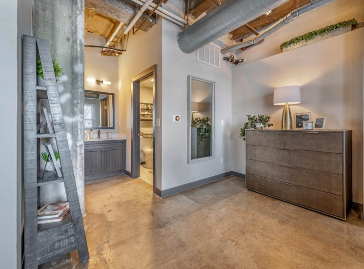 Industrial Style Apartment Bathroom with  Exposed Concrete, Decorative Shelf, Grey Wood Cabinets and White Cabinets Under Mirror Next to Bathroom Door and Full Length Mirror NExt to Dress with Plants and Decorations