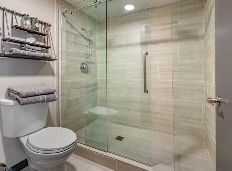 Model Bathroom with Floating Shelf Over Toilet with Towels and Decorations Next to Glass Enclosed Shower with Barn Door Style Sliding Door