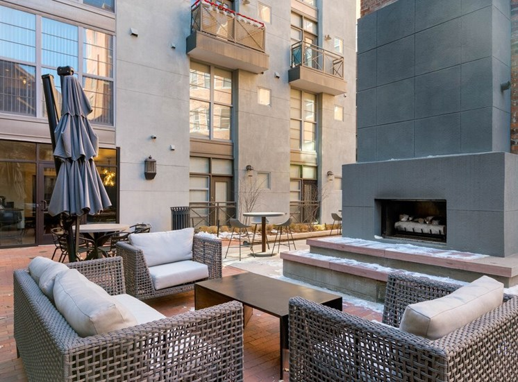 Courtyard Lounge with  Concrete Fireplace Surrounded by Patio Couch and armchairs with Cushions and Coffee Table Next to Building