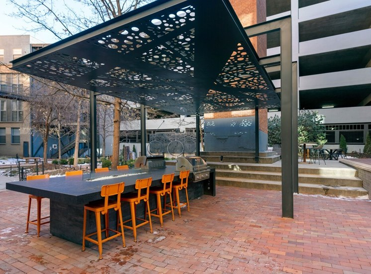 Brick Courtyard Lounge Area  with Contemporary Grilling Station with Bar Counter and Orane Stools Under Metal Decorative Black Metal Covering with Building and Parking Garage in the Background
