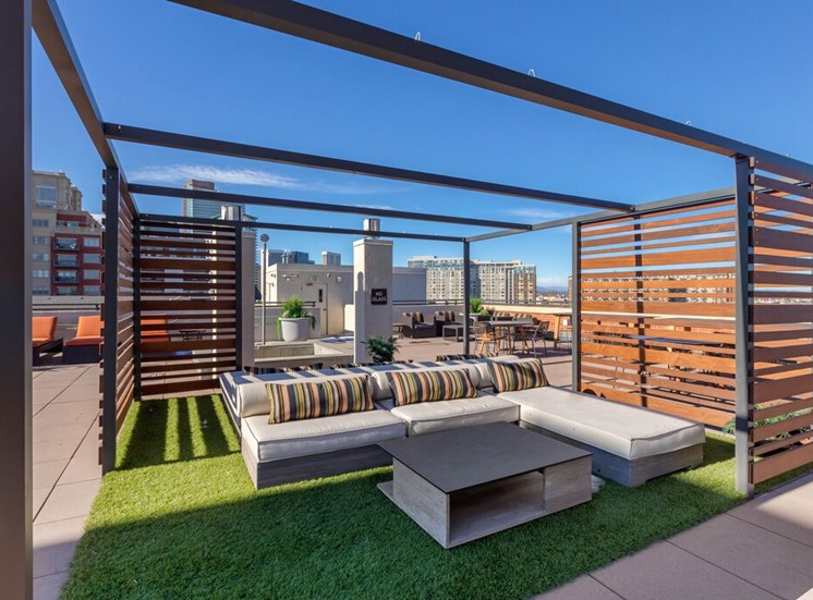 Rooftop Terrace Lounge with Cushioned Patio Sectional  on Grass with Patio Coffee Table Surrounded by Decorative Metal and Wood Partial Enclosure, with Orange Cushioned Lounge Chairs and City View in the Background