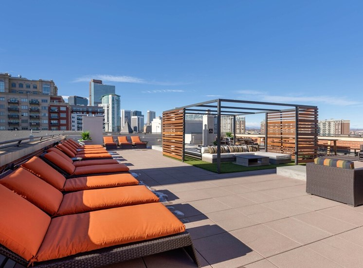 Rooftop Terrace Lounge with Cushioned Patio Armchairs Surrounded by Decorative Metal and Wood Partial Enclosure, Orange Cushioned Lounge Chairs with City View in the Background