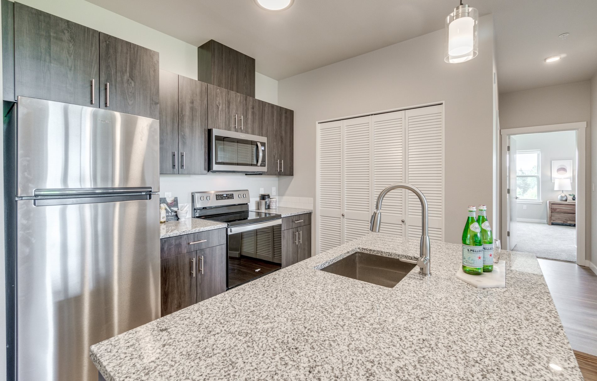 view of kitchen with dark cabinet and stainless steel appliances. Microwave over stove.