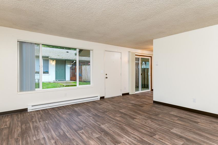 Pinewood Terrace Apartments   Living Room with large window, front door and view of patio sliding door in dining room.