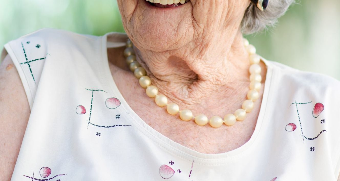 Smiling grandmother with pearls.