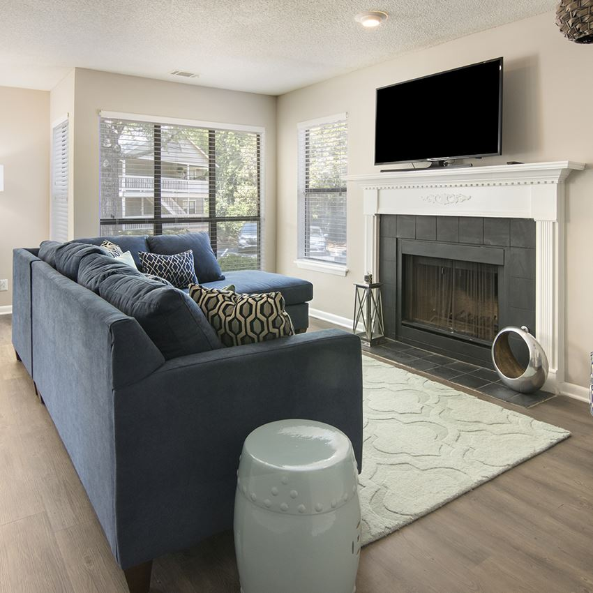 Model living room with an L-shaped couch facing a fireplace with a TV hung above it in Forest Pointe Apartments in Macon, GA