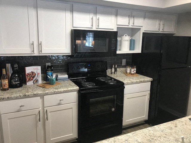 apartment in tallahassee with modern kitchen featuring white cabinets and black appliances
