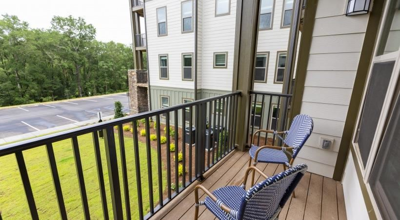 Private patio and balcony with two chairs at The Retreat at Fairhope Village in Fairhope, AL