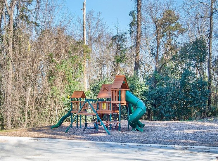 view of trees and playground at Magnolia Crossing apartments in Macon GA