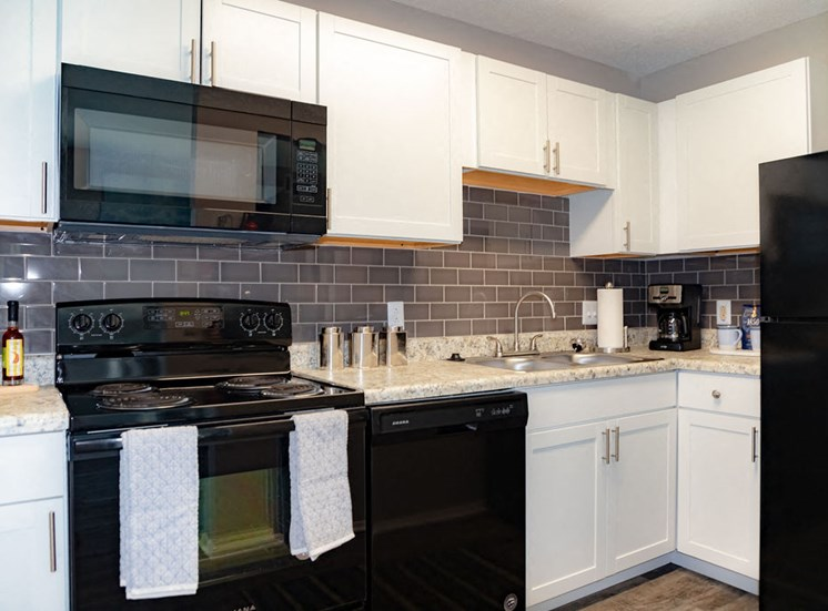 Macon GA apartment kitchen with white cabinetry and black appliances