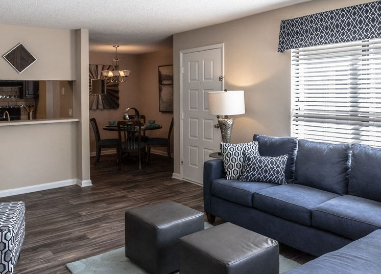 Living room with dining area and kitchen through wall at Forest Pointe apartment