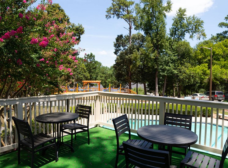 balcony with black tables and chairs overlooking pool area at Macon GA apartments
