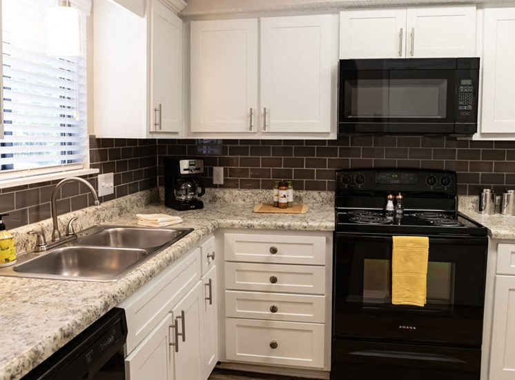 apartment kitchen with white cabinets black stove and microwave