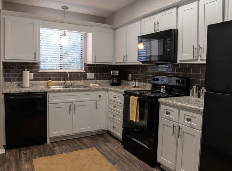 Macon GA apartment kitchen with black appliances and white modern cabinets