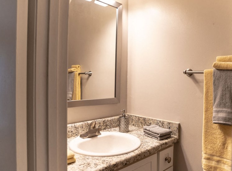 close view of apartment bathroom with sink mirror and yellow towels