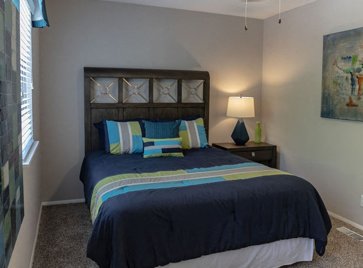 bedroom in an apartment in Macon with navy blue bedding and brown headboard