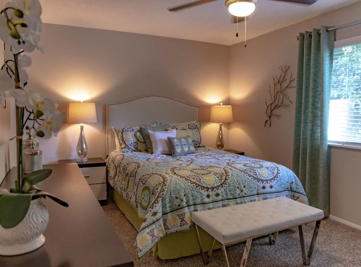 furnished apartment bedroom with neutral carpet ceiling fan and window