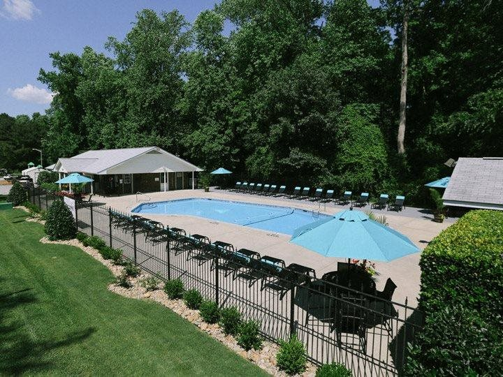 overview of fenced-in pool with poolside chairs at apartments in Greenville NC