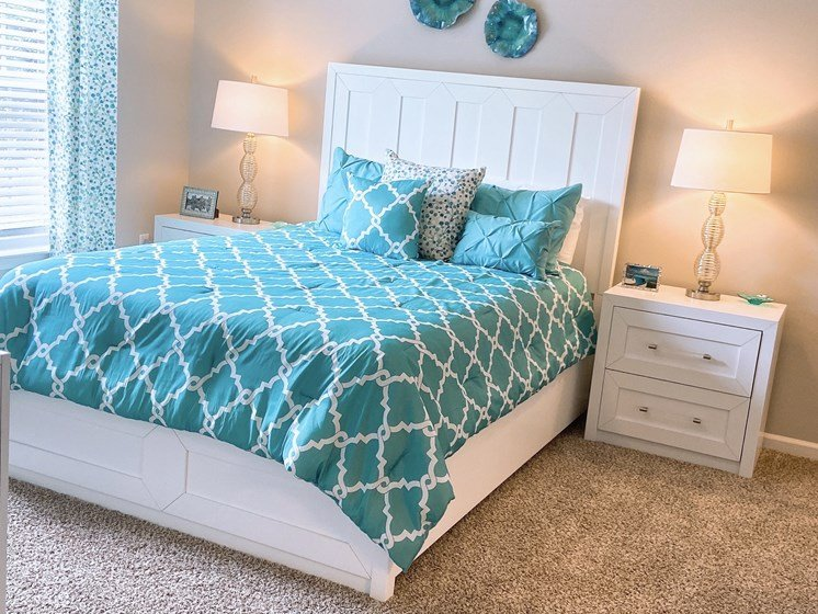 furnished master bedroom in a Fayetteville apartment with plush carpeting
